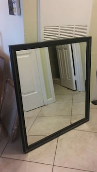 rectangular black framed wall mirror