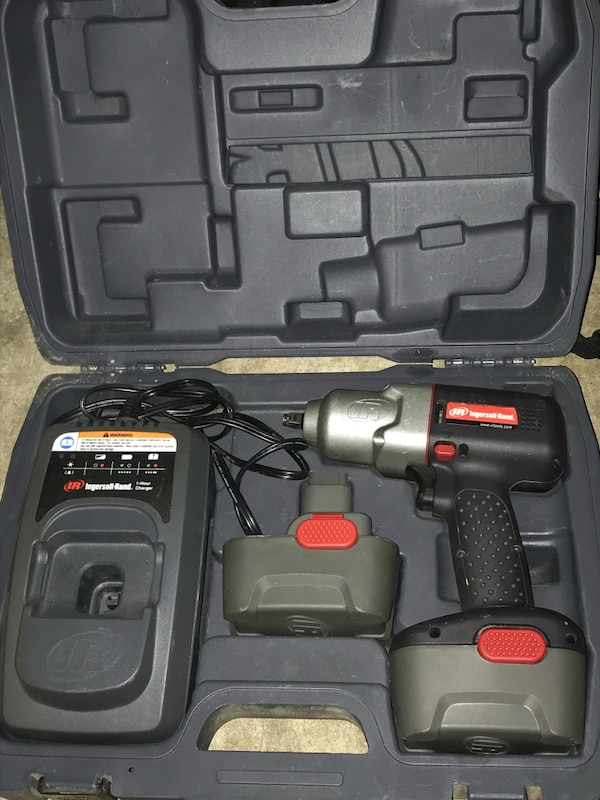 gray and black cordless drill with battery pack, charger, and case