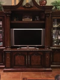 """Dark stain Entertainment Center with two glass glass doors for all your heirlooms.  No scratches, glass in perfect condition . 7'5"""" x 11'6"""""""