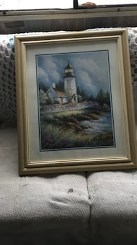 Brown wooden framed painting of lighthouse near body of water