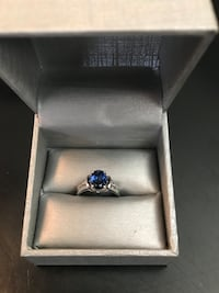 Silver-colored blue gemstone ring with gray case. Necklace sold