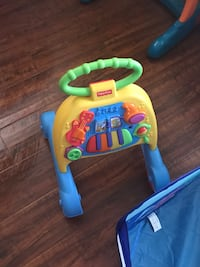 baby's yellow, green, and blue Fisher-Price sit to stand activity walker