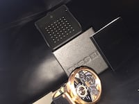 round gold-colored chronograph watch with black leather band 563 km