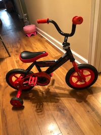 toddler's black and red bicycle with training wheels
