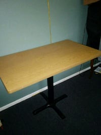 Brown wooden table with black metal base