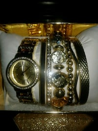 round gold-colored analog watch with link and six gold-colored bracelets