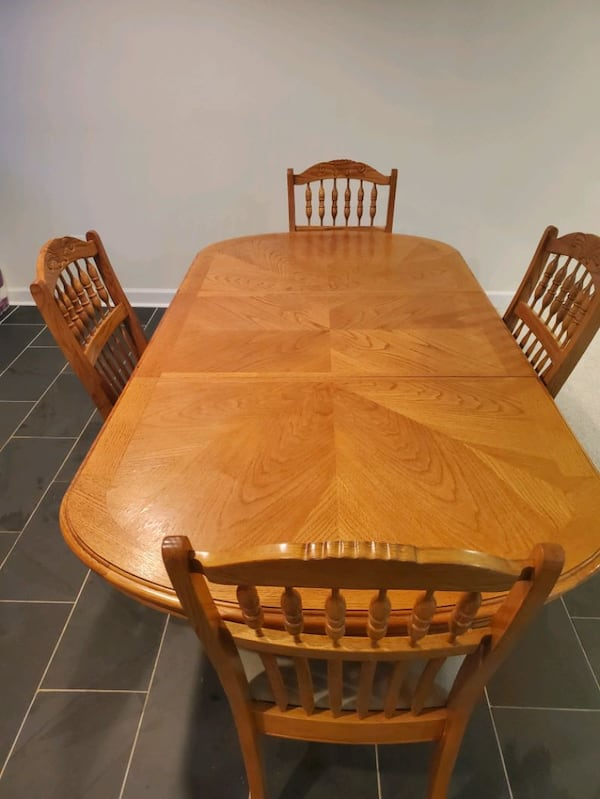 Dining Room Set.  Wood finish and centerpiece extension.  Four chairs. 9b1d55e5-25cc-43f9-bdd7-d4ba7427bf87