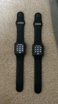 Two space gray aluminum case apple watches with black sport band