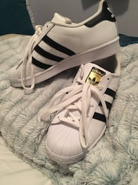 pair of white-and-black Adidas Superstar shoes
