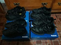four pairs of black Reebok sneakers on boxes