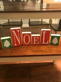 "Reversible wooden blocks. One side says ""FALL"" in orange and yellow. Other side says ""NOEL"" in red and green. Crofton, 21114"