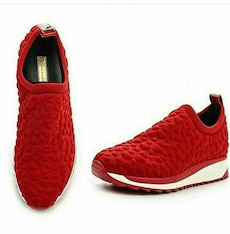 pair of studded red slip on running shoes
