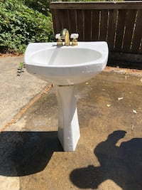 White ceramic pedestal sink with faucet