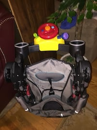 Black and gray stroller with toy attachment