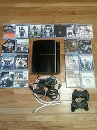 black Sony PS3 with controllers and game case