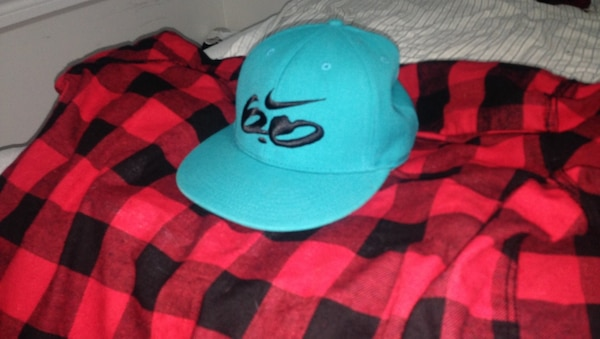 teal Nike fitted cap and black and red gingham flannel top