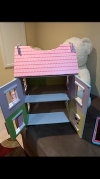 white and pink wooden dollhouse