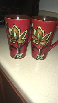 two red floral ceramic mugs