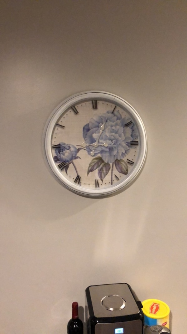 round white and blue floral analog wall clock