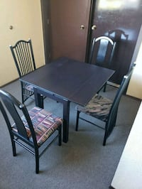 Small black wooden table with four chairs di Richmond, V7A 4N3