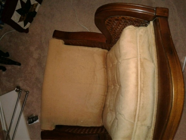 brown wooden framed padded armchair adcb54d6-6663-4fa5-95e4-24163005fc76