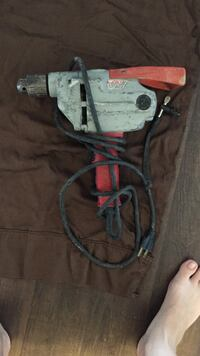 Drill. Gray and red corded power tool