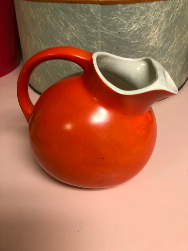 red and white ceramic pitcher