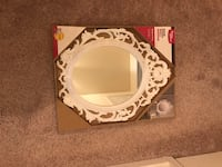 white ornate framed wall mirror with box