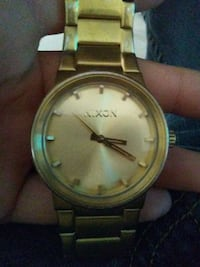 round gold-colored Nixon analog watch with link band 1622 mi