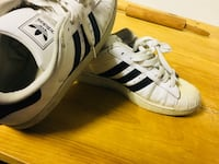 pair of white-and-black Adidas Superstar low-top sneakers