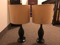 two black base table lamps with beige lampshades