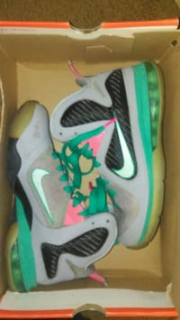 pair of gray-and-green Nike basketball shoes
