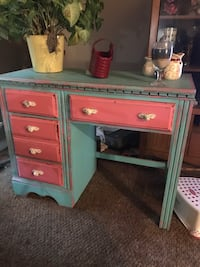 red and green wooden single-pedestal desk