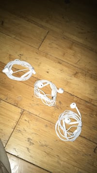 two white and pink corded headphones