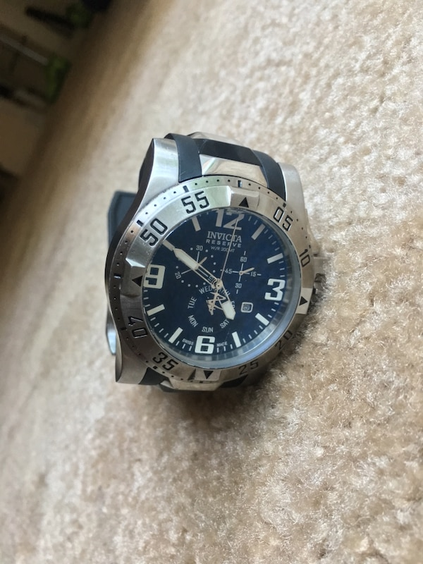round silver Invicta chronograph watch with black strap