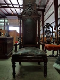 brown wooden framed black leather armchair