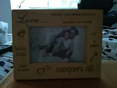 brown wooden Love conquers all printed frame