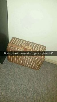 wicker brown picnic basket with cups and plates
