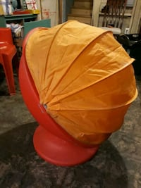 Retro red Ikea Egg Pod chair on swivel with yellow cover.