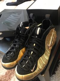 Pair of black-and-gold nike foamposite shoes