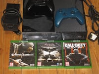 black Xbox One console with controller and game cases Atlanta
