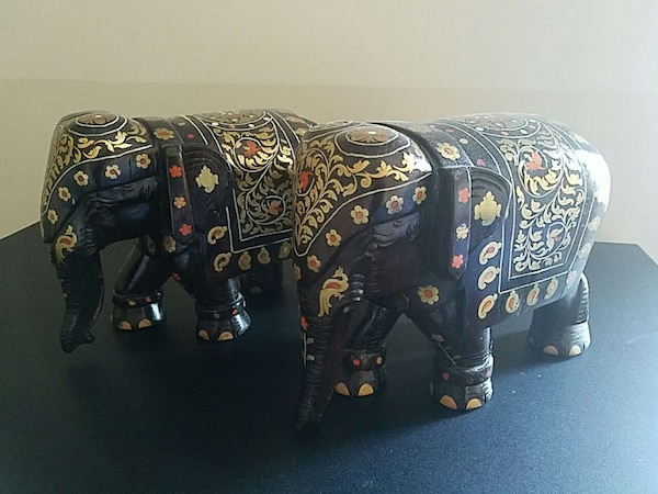 two dark solid wood, gold and orange elephants