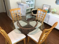 brown wooden framed glass top table with chairs