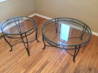 Two round glass-top with black metal base coffee tables
