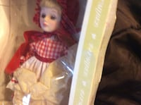 girl in blonde hair, red headscarf, and red and white dress porcelain doll with box