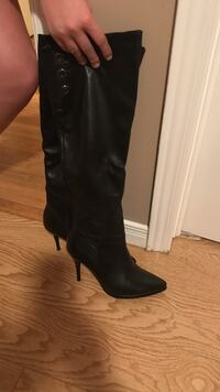 pair of black leather pointed-toe heeled knee-high boots