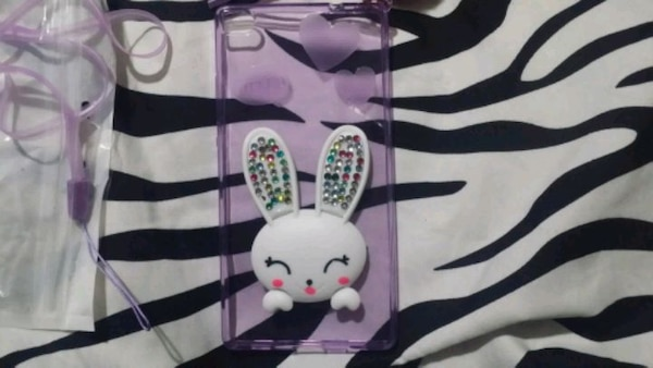 white and purple phone case. Not sure what kind of phone it's for. 9ba53034-5074-457f-9b67-11cfa51f090f