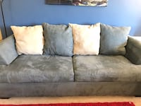 Gray blue suede sectional couch with ottoman with the black color table