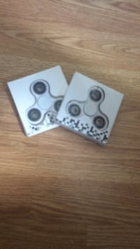 two white fidget spinners in boxes