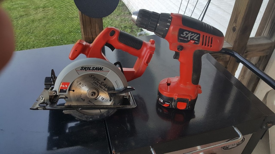 Red and black Skil cordless hand drill and Skilsaw